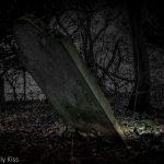 Broken grave in pool of light