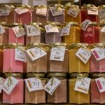 Rows of coloured honey in jars