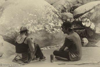 Girl and boy sitting on rocks drinking