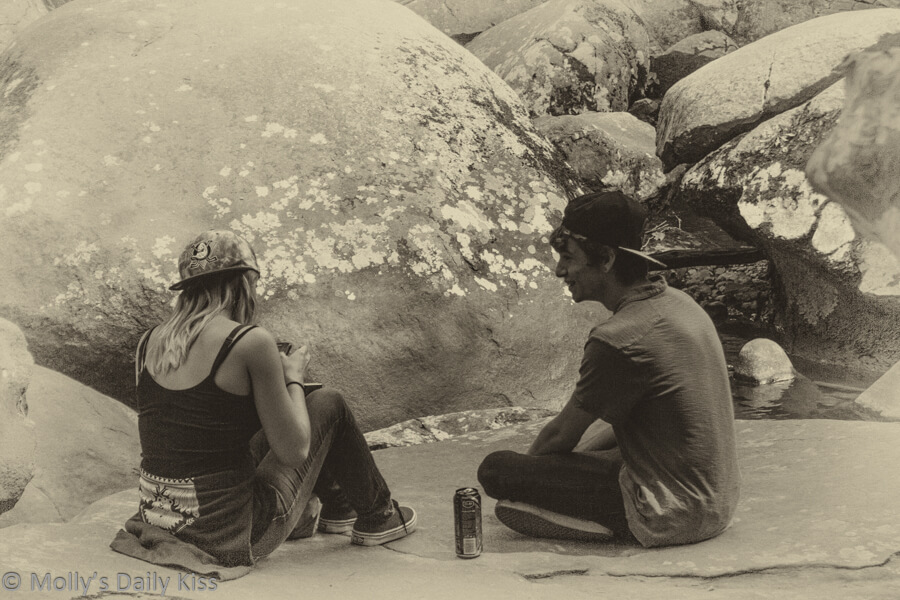 Girl and boy sitting on rocks drinking