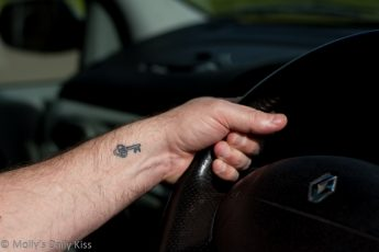 Man with key tattoo holding steering wheel