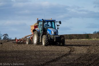 Tractor chuggin along sowing seeds in field