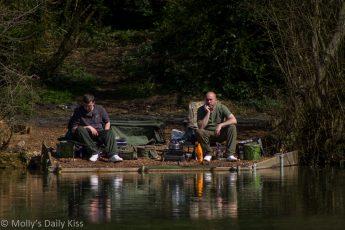 Men sitting by pond fishing taking in serenity