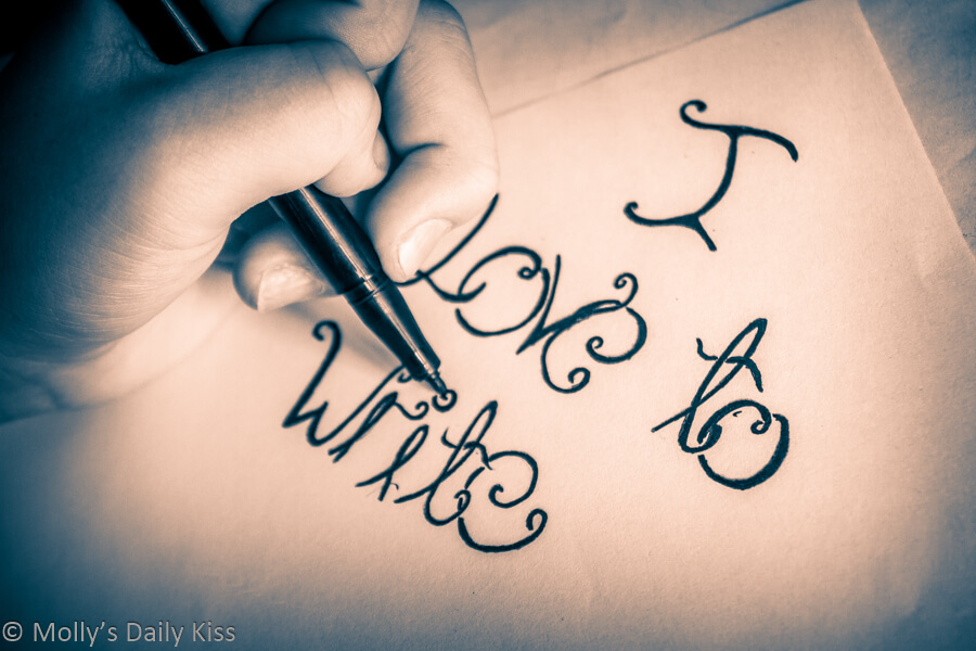 Swirl of text on paper with pen writing words