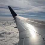 View from jet plane across the wing and clouds