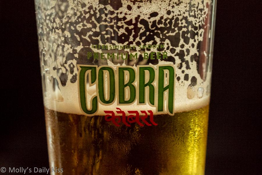 crisp cold Cobra beer in glass half full