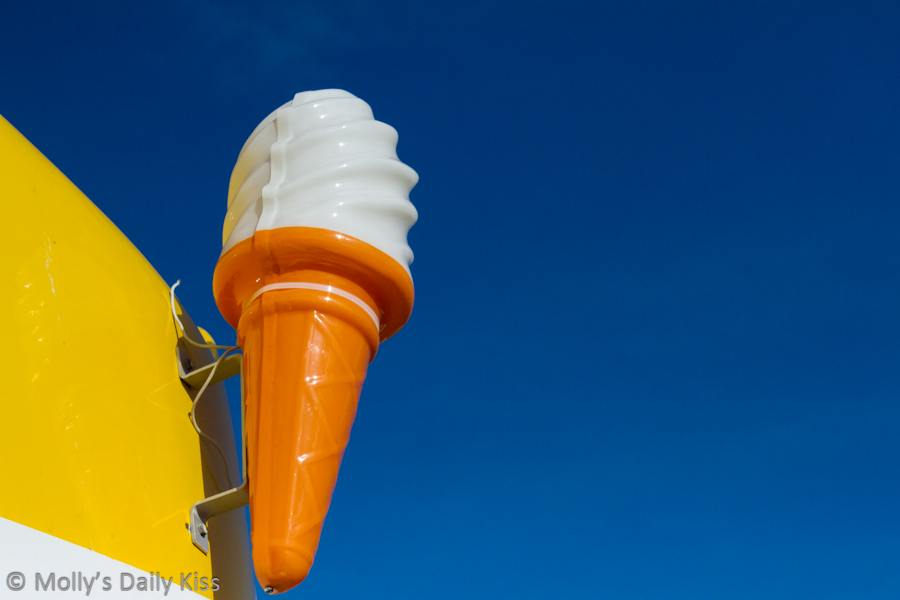 Plastic icecream sign against blue sky