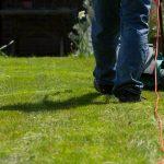 Man mowing cut grass