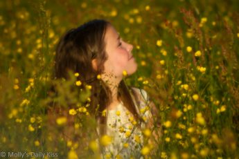 Young girl sitting in a field of buttercups that little cups of gold