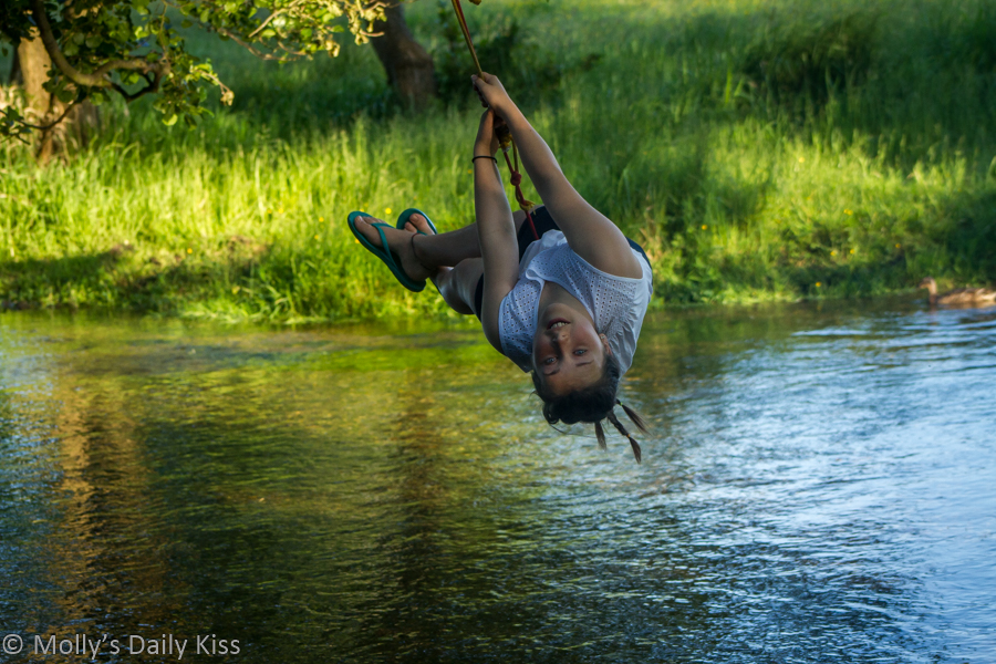 Child on rope swing over river having fun