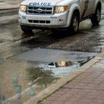 police car reflection in street mirror of rain