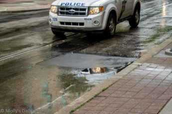 police car reflection in street mirror of rain