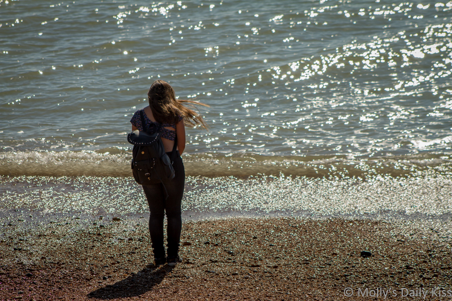 Young girl standing on the shore contemplate the ocean