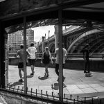 Runners on the embankment reflected in window makes a multidimensional image