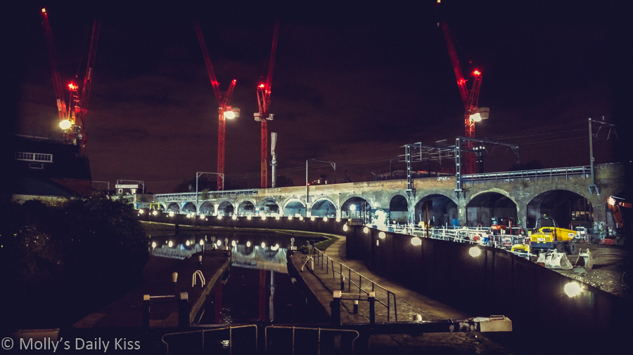 Construction reflected in Regents Canel London at night. A City regenerating
