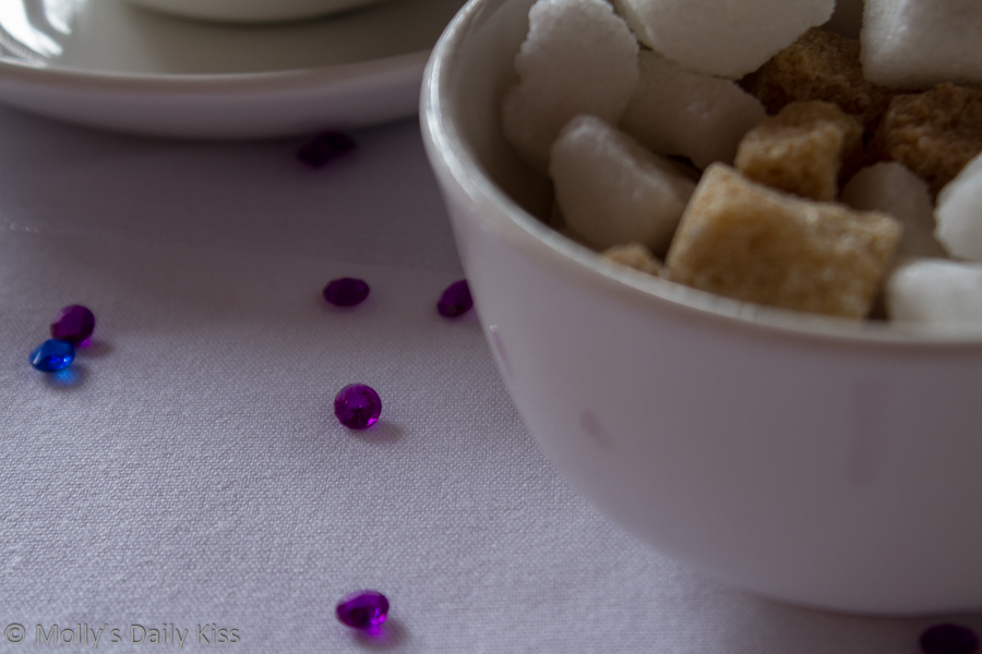 White bowl with white and brown sugar cubes