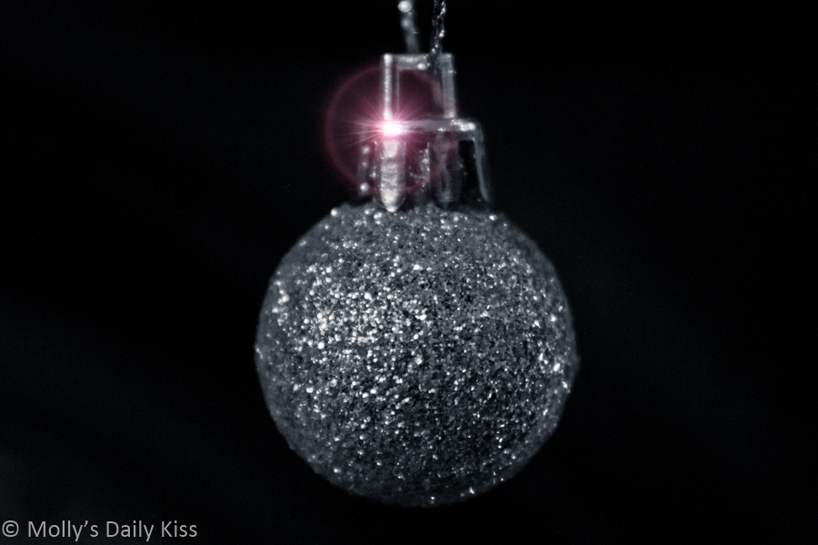 silver glitter Christmas tree bauble with burst of light glisten on the top on the top