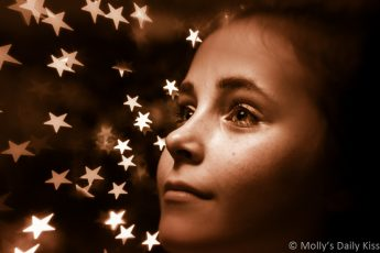 Portrait of young girl in front of Christmas tree stars taken with Lens Baby