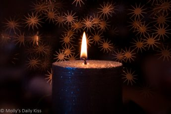 Single candle flame against bokeh star back ground. Image name define the darkness