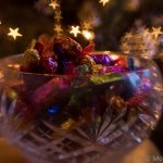 Quality Street chocolates in a bowl with Christmas tree bokeh lights