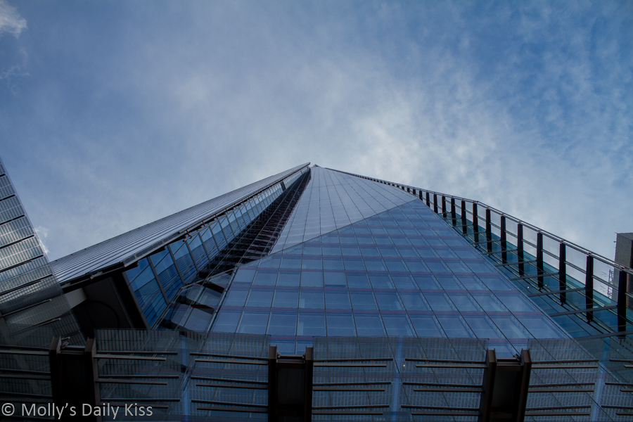 Looking up the outside of the Shard in London to blue skies. Towers over london