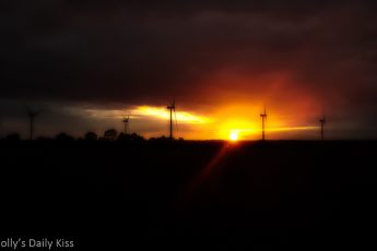 Sunset silhouetting windfarm windmills. The sun, the giver of life