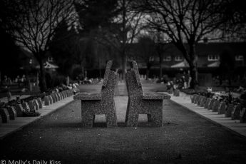 black and white of stone benches back to back in cemetary, A place for resting