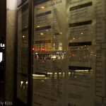 impersonal city lights reflected in bus timetable kings cross