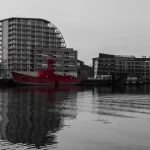 red boat waiting in dock, colour splash reflected in docklands london