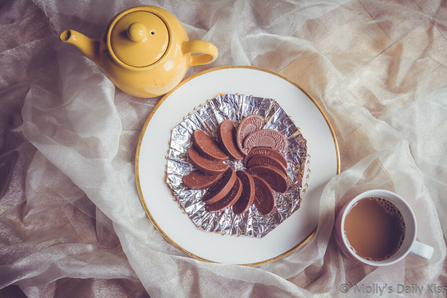 Chocolate orange faned out on a plate with tea mug and pot