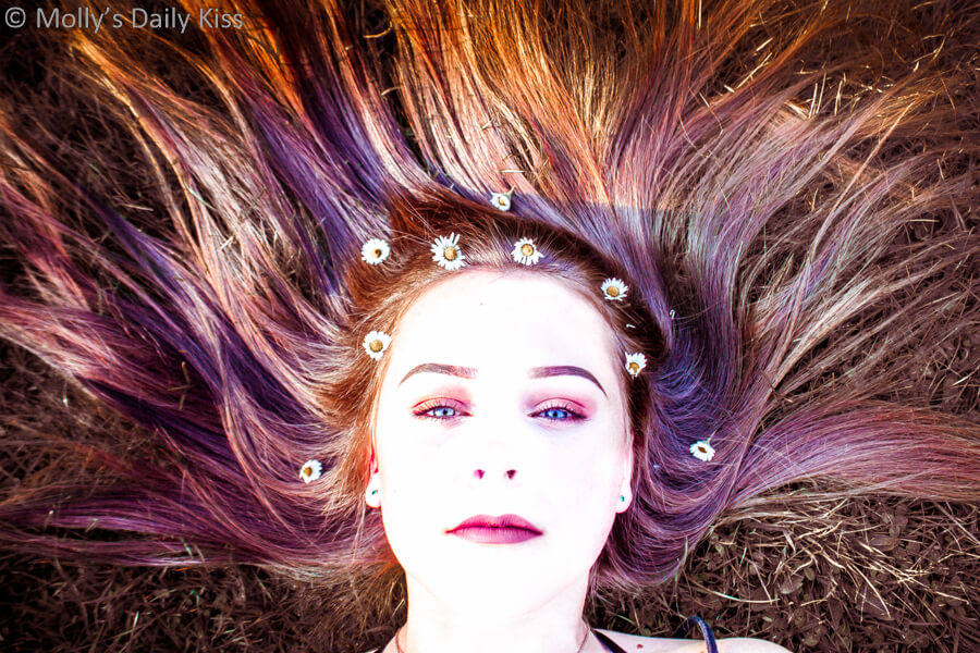 Young girl with hair splayed out around her with flowers in her hair and multi coloured hair