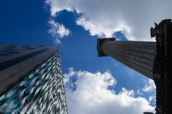 Looking up the old Monument in London next to new modern building