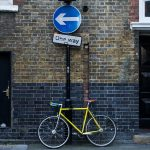 Yellow bicycle chained up on one way sign in Hoxton London