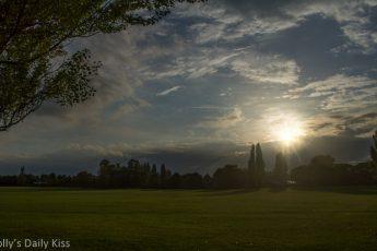 sun burst through dark clouds over parkland. Good things