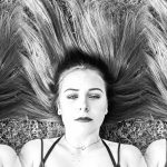 Black and white triptych of girl with hair fanned out around her. My little