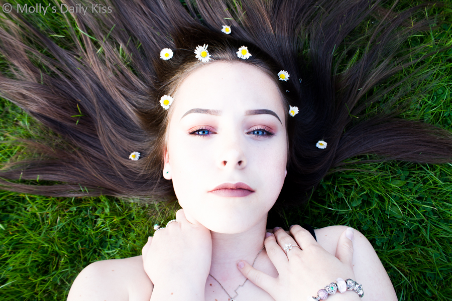 Girl laying on grass with flowers in her hair and blue eyes. Secrets in her eyes