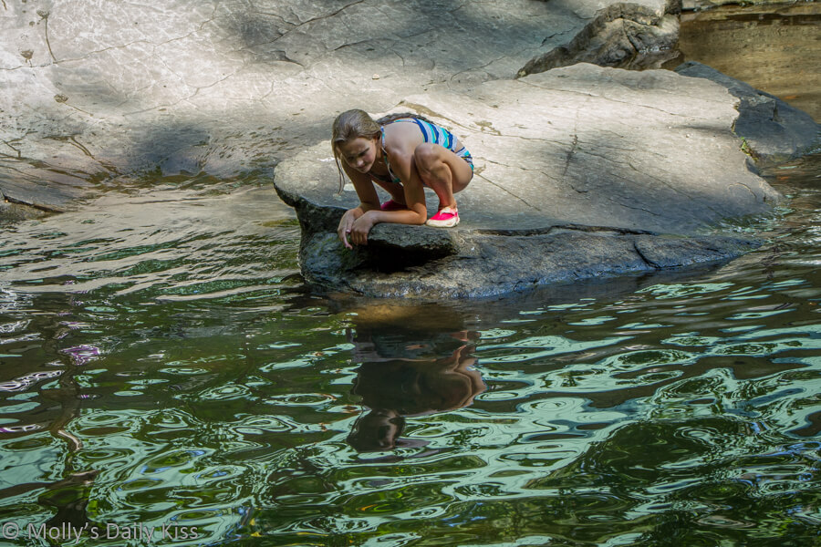 Young girl on rock looking into water
