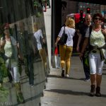 Woman reflected in glass building as they walk down the road. Looking glass london