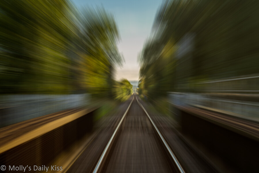 Looking down train track with movement creating blur. The Journey