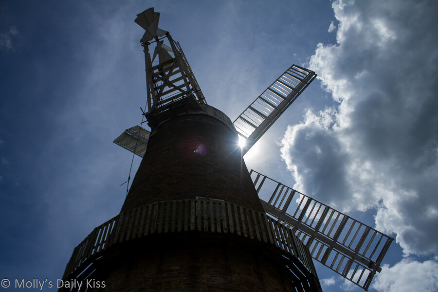 Windmill silhouette wtih sun bursting through the sails and high blue sky beyond
