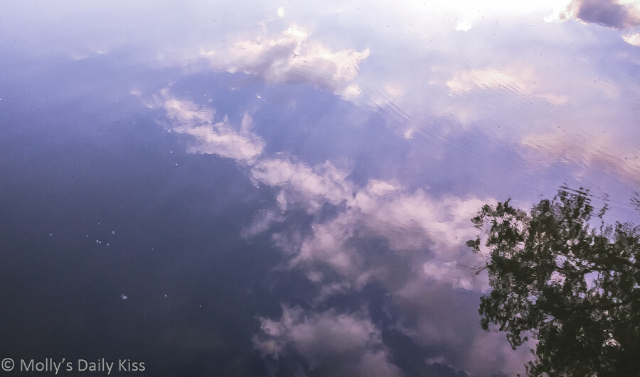 clouds in blue sky floating in water reflection