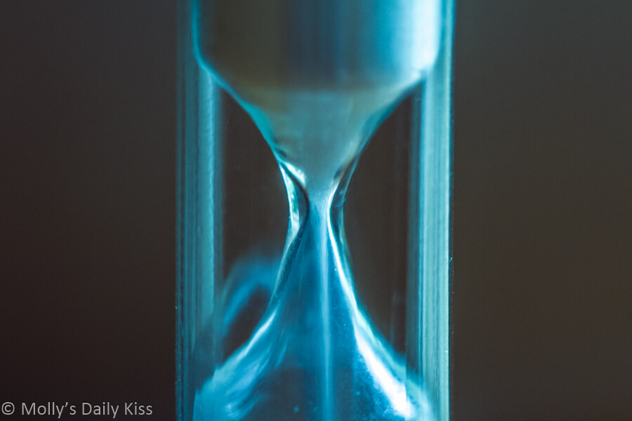 Macro shot of sand running through an hourglass