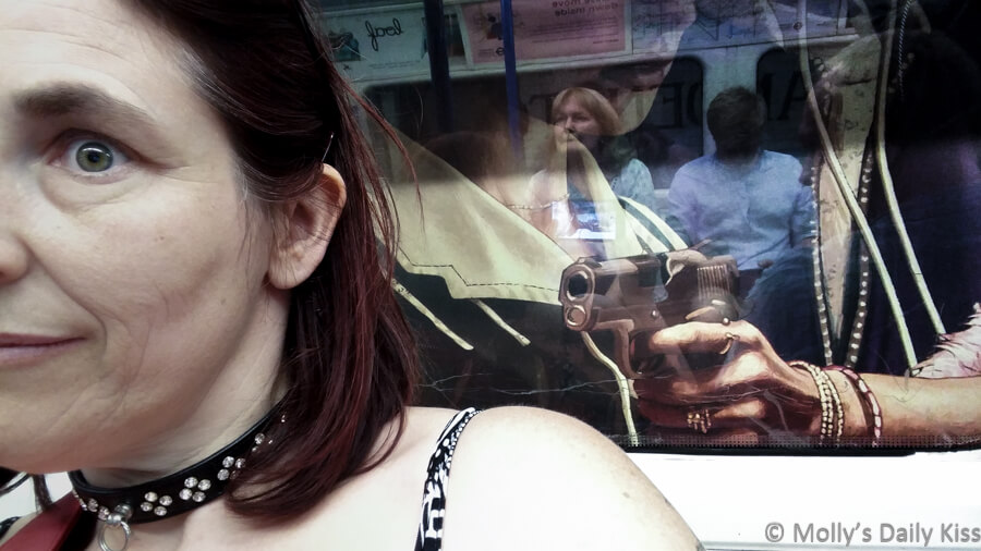 Self portrait of Molly with poster of man holding gun to her back behind her in the London Underground