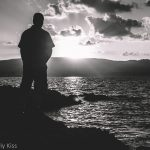 black and white image of man standing on rocks watching sunset. Image title Step to the edge