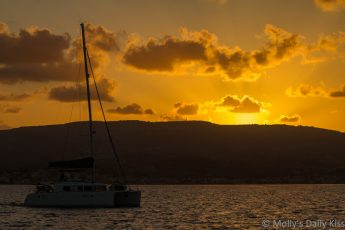 Sunset over Argostoli bay Kefalonia as sailing boat comes in from the Aegean