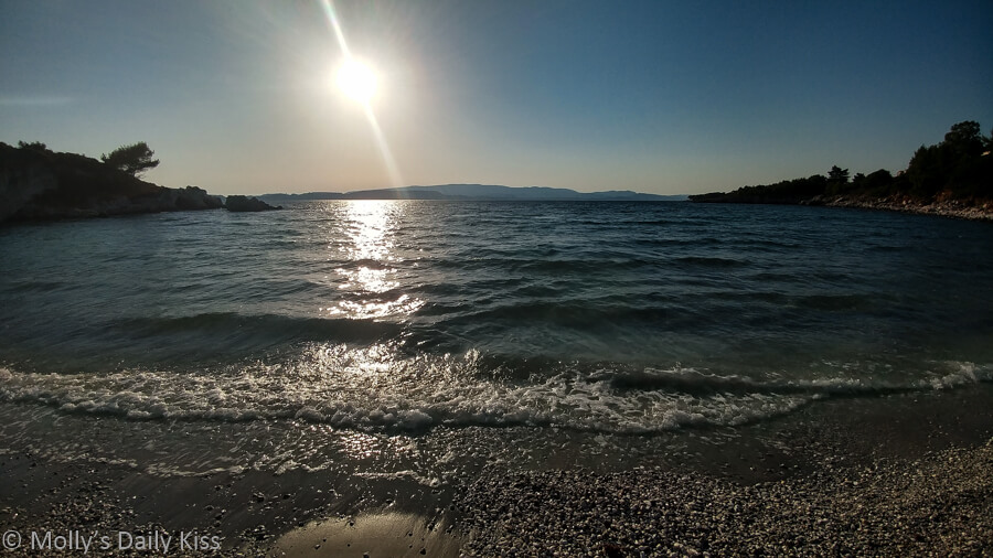 Sun creating a line of light down into the sea at the beach in Kefalonia