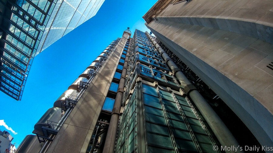 Looking up to the blue sky between the straight line of Lloyds of London and the Leadenhall building London.