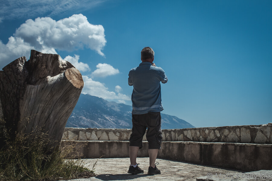 man taking photograph of blue sky and mountains in kefalonia. The trip was worth it