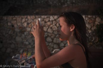 girl captured in photograph taking a photograph of the sunset