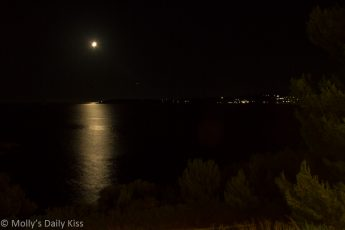Bright moon in sky with moonlight reflecting on the sea kefalonia